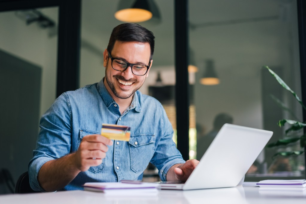 Healthcare credit card processing occurring at a mental health clinic as a happy man makes an online credit card payment.