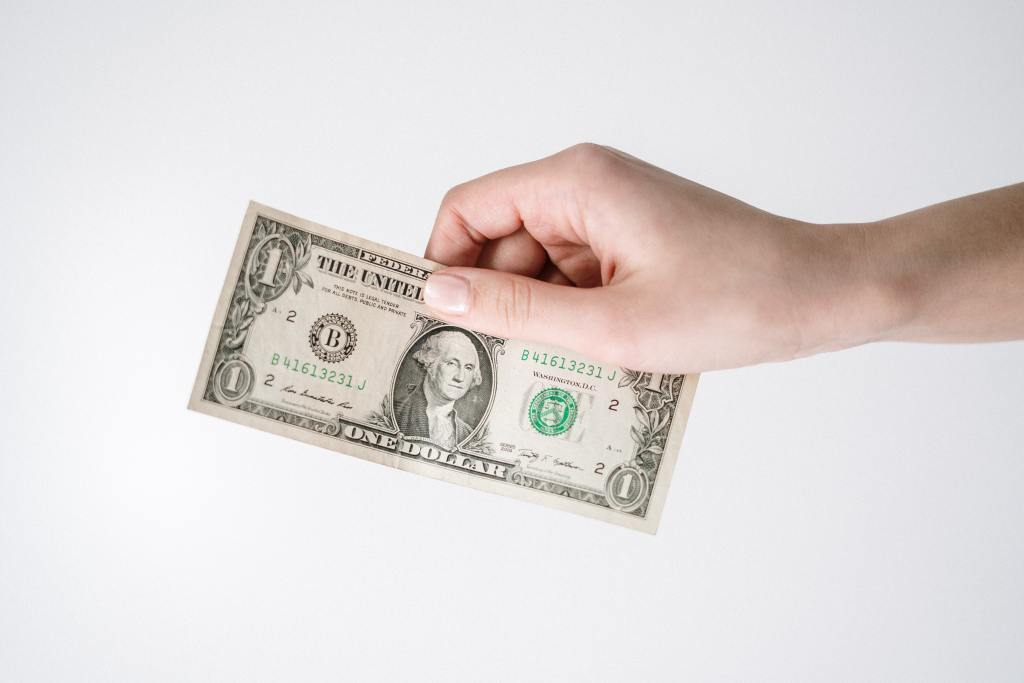 Money in a hand representing the benefits understanding the healthcare revenue cycle can have on cashflow.