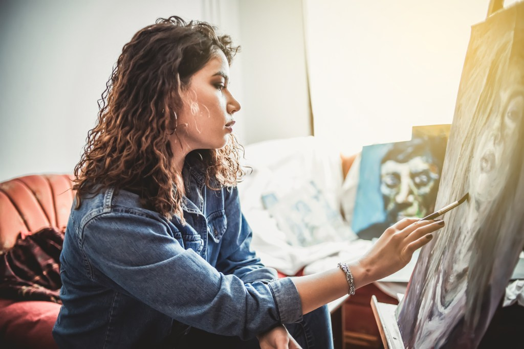 Behavioral health patient painting a self-portrait in an art therapy session.